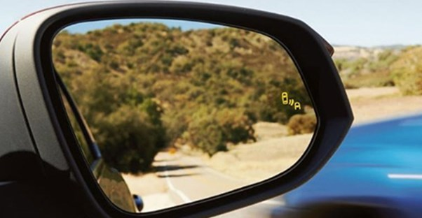a car with blind spot monitoring in the mirror