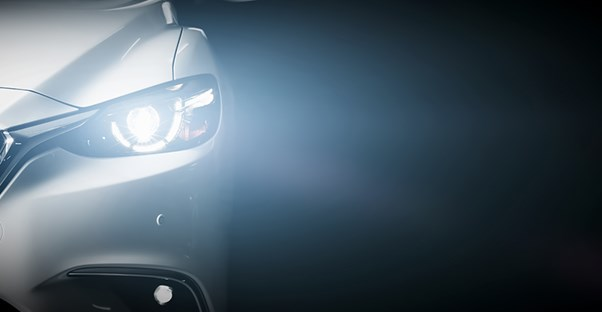 the headlight of a luxury car shines toward the camera