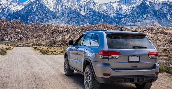 a hybrid suv makes its way down a dirt road toward mountains