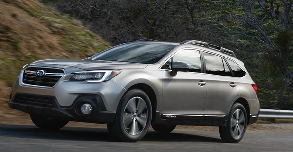 a gray 2018 subaru outback travels down the road