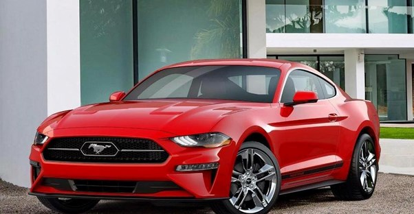 a red 218 ford mustang in a driveway