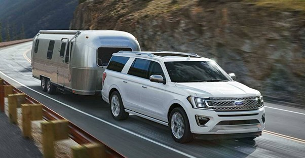 a white 2018 ford expedition pulling an airstream