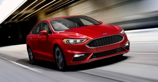 a red 2018 ford fusion driving down the street