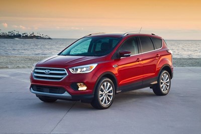 a red 2018 ford escape in front of the ocean