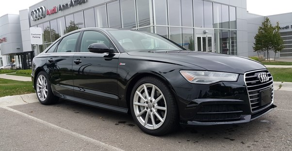 a black 2018 audi a6 in front of a dealership