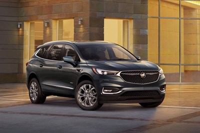 a black 2018 buick enclave in the driveway of a modern house
