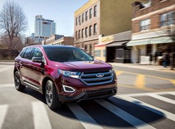 a maroon 2018 ford edge drives down a city street