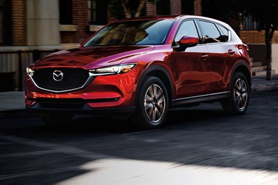 a red 2018 mazda cx-5 driving down the road