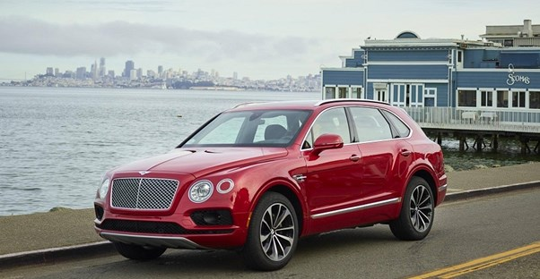 a red 2018 bentley bentayga driving down a road next to the ocean