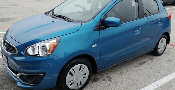 a blue mitsubishi mirage sits in a parking lot