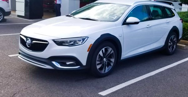 a white 2019 buick regal tourx in a dealership parking lot