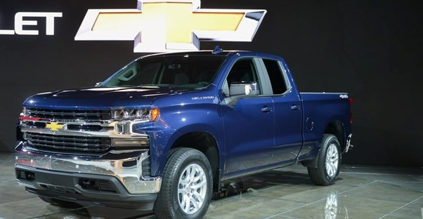 a blue 2019 chevrolet silverado 1500 on an auto show stage
