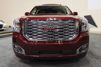 a red 2019 gmc yukon at an auto show