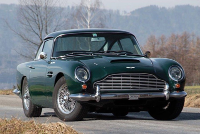 A dark green Aston Martin DB5 driving down a road