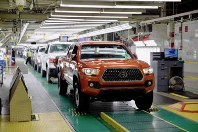 a 2019 orange toyota tacoma on the assembly line