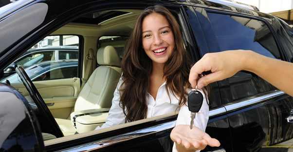 a woman who is happy she avoided mistakes when buying her new car