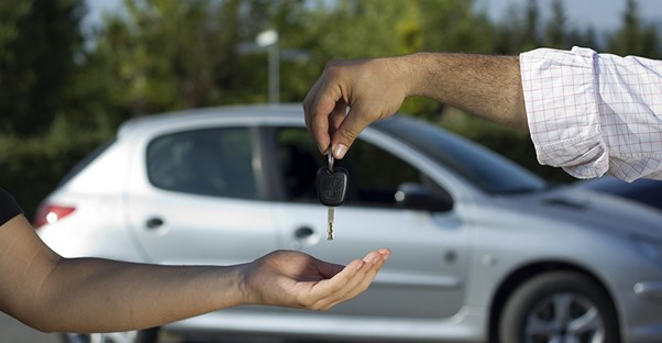 Car dealer handing over the keys to a new car purchased through financing