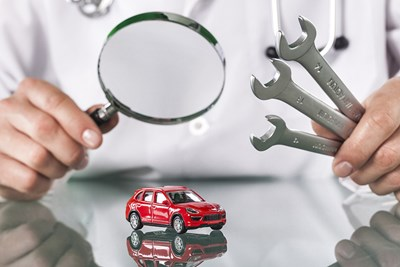 Car doctor examining a miniature broken car with tools