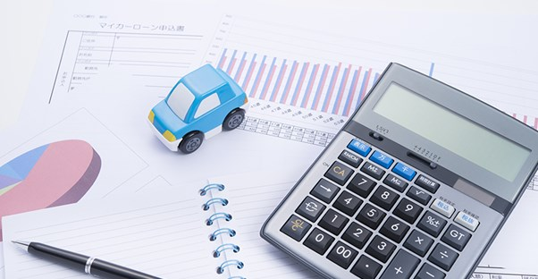 calculator and car on notebook pen and auto loan paperwork