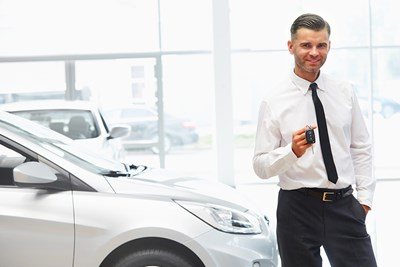 guy holding car keys to new car after getting an auto loan