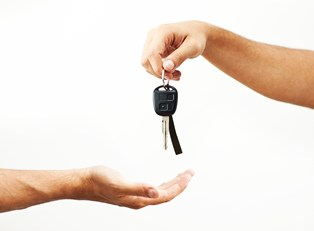 hand extending car keys to an outstretched hand