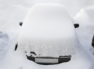 A car covered in snow because it doesn't have a car cover