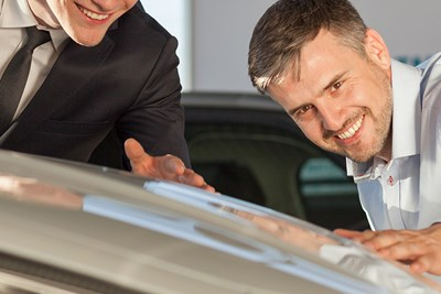 two guys giving a car an appraisal
