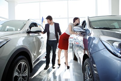 man and woman inspecting different cars