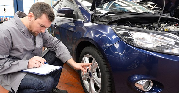 guy studying a new car and looking at paper