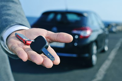 person holding keys to new car